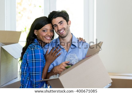 Portrait of young couple carrying cardboard box in their new house - stock photo
