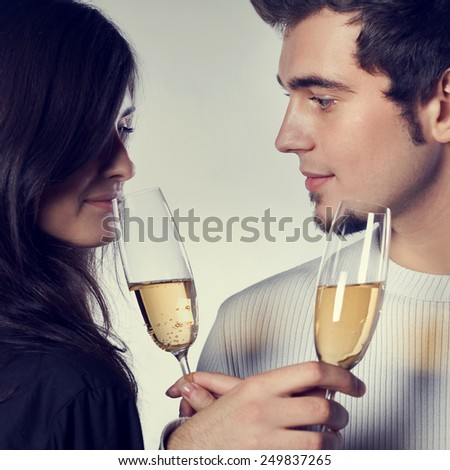 Portrait of young couple celebrating with champagne - stock photo