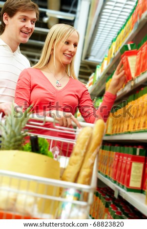 Portrait of young couple choosing pack of juice - stock photo