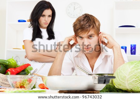 portrait of young couple conflict in their kitchen, relationship problem, negative emotion, angry woman with folded hands looking to sad man - stock photo