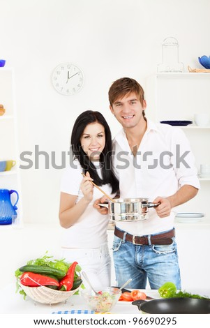 portrait of young couple cooking, in their kitchen happy smile, looking at camera, hold pan with ready meal, soup, boiler - stock photo