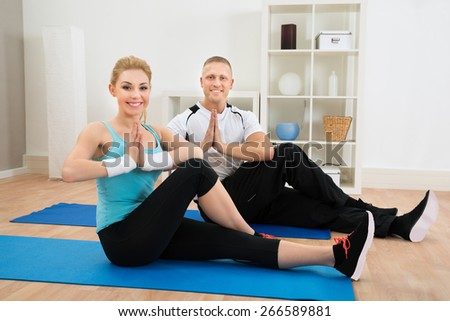 Portrait Of Young Couple Doing Yoga On Exercising Mat - stock photo