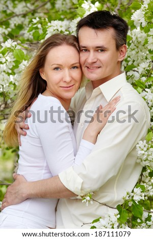 Portrait of young couple embracing and looking at camera in park - stock photo