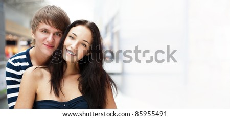 Portrait of young couple embracing at shopping mall and looking at camera. Horizontal shot. Lots of copyspace - stock photo