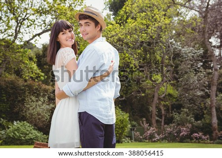 Portrait of young couple embracing each other in garden - stock photo