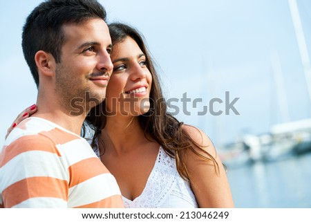 Portrait of young couple enjoying late afternoon sun in harbor.