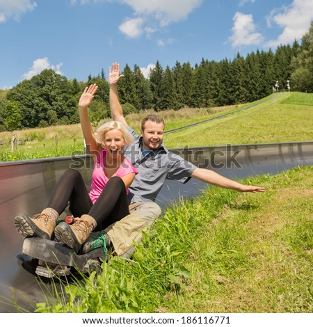 Portrait of young couple enjoying summer sledge ride - stock photo