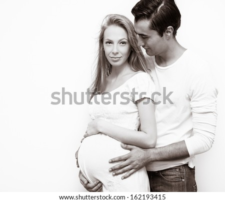 Portrait of young couple expecting baby - stock photo