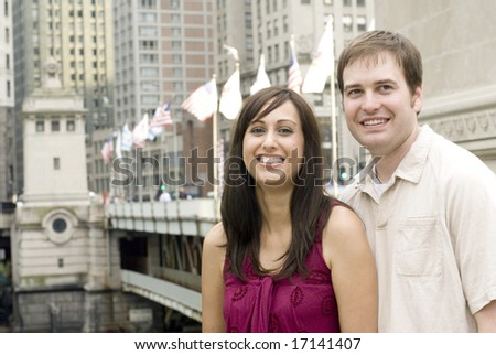 Portrait of young couple grinning withÃ?bridge behind them - stock photo