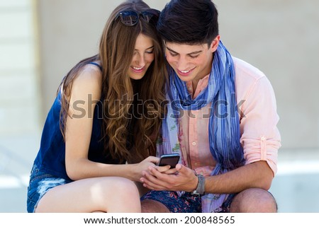 Portrait of Young couple having fun with smartphones, outdoors