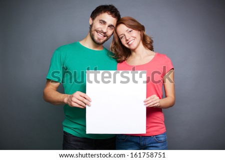 Portrait of young couple holding blank paper and looking at camera