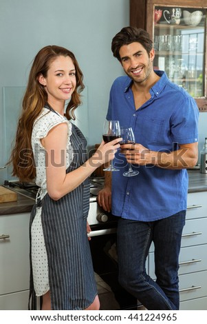 Portrait of young couple holding wine glass in kitchen at home