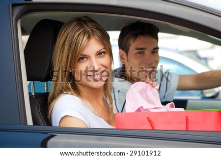 portrait of young couple in car after shopping - stock photo