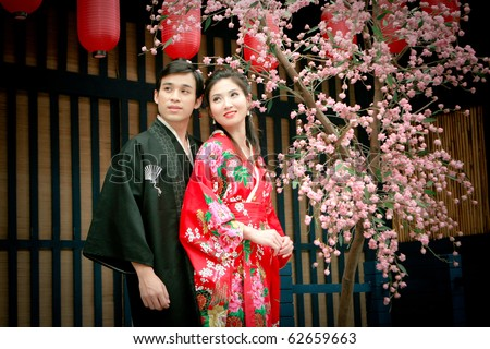 Portrait of young couple in japan dress looking to sky - stock photo
