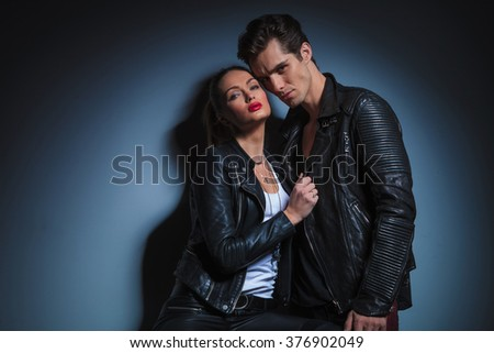 portrait of young couple in leather jackets posing in dark studio background. the man is leaning on woman while she is pulling his jacket looking at the camera - stock photo