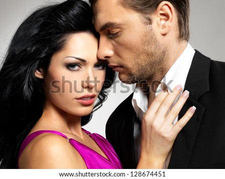 Portrait of young couple in love posing at studio dressed in classic clothes
