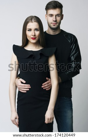 Portrait of young couple in love posing at studio dressed in stylish clothes - stock photo