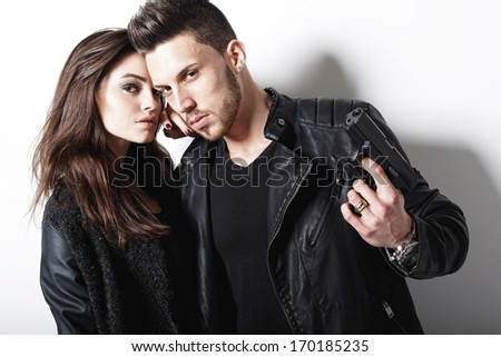Portrait of young couple in love  with gun posing at studio.Fashion photo. - stock photo