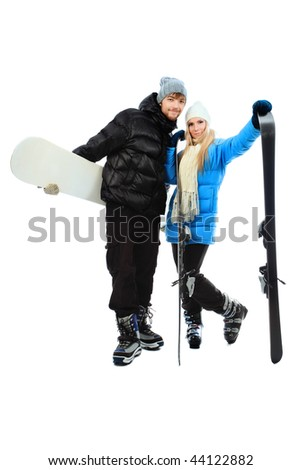 Portrait of young couple in warm clothes holding skis and snowboard.