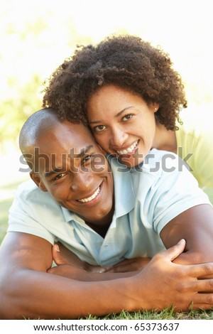 Portrait Of Young Couple Laying On Grass In Park - stock photo