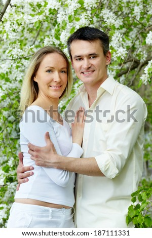 Portrait of young couple looking at camera in park - stock photo