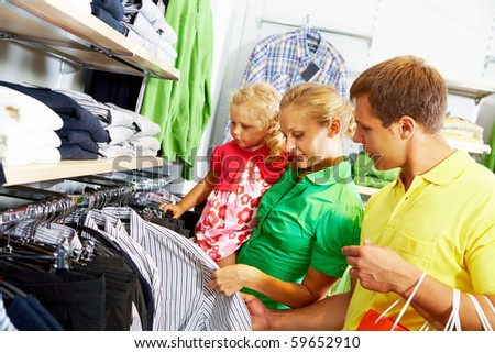 Portrait of young couple looking at clothes with their daughter in the mall - stock photo