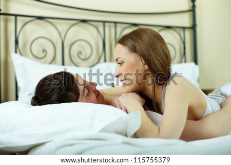 Portrait of young couple lying in bed and looking at one another - stock photo