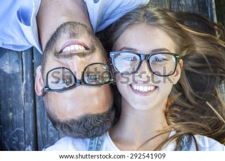 portrait of young couple lying on wooden bench - stock photo