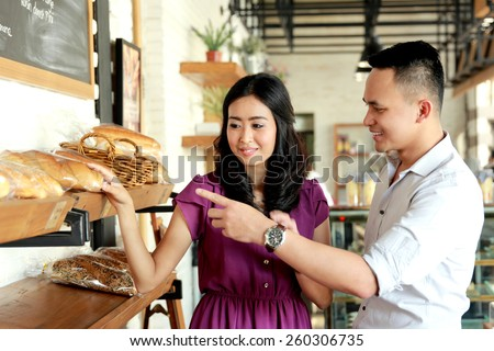 portrait of young couple make a choice to bread they will buy - stock photo