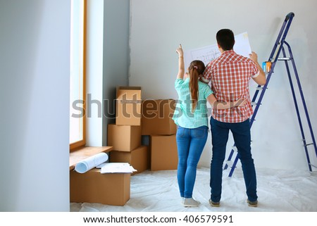 Portrait of young couple moving in new home - stock photo