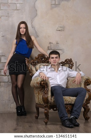 Portrait of young couple posing on the vintage sofa