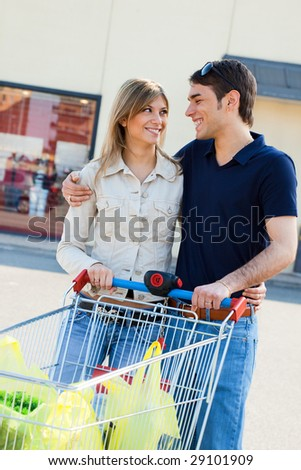 portrait of young couple pushing shopping cart outdoors - stock photo