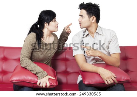Portrait of young couple quarreling and blaming each other, isolated on white - stock photo
