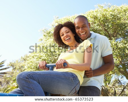 Portrait Of Young Couple Riding On SeeSaw In Park - stock photo