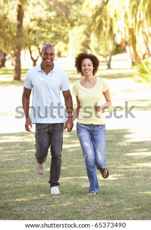Portrait Of Young Couple Running Through Park - stock photo