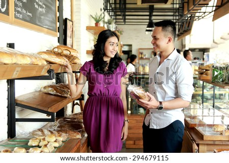 portrait of young couple shopping at bakery shop