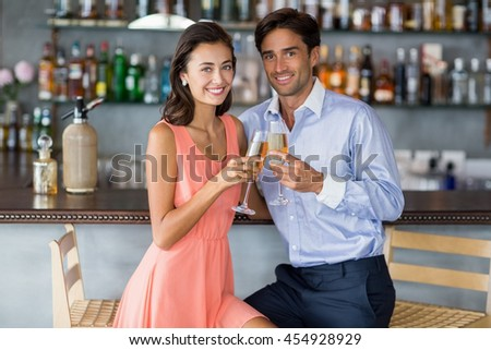 Portrait of young couple sitting at bar counter and toasting a glasses of champagne at restaurant