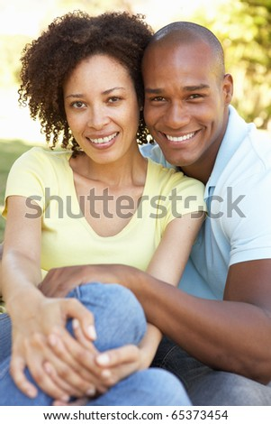 Portrait Of Young Couple Sitting In Park - stock photo