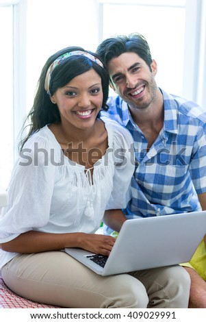 Portrait of young couple sitting on bed and using laptop at home