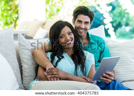 Portrait of young couple sitting on sofa and using digital tablet at home