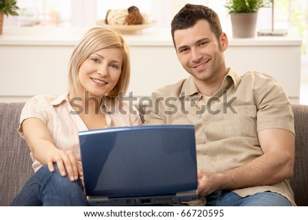 Portrait of young couple sitting on sofa holding laptop smiling at camera.?