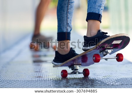 Portrait of young couple skateboarding in the street.