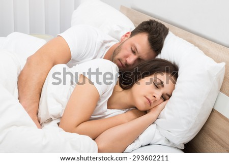 Portrait Of Young Couple Sleeping On Bed