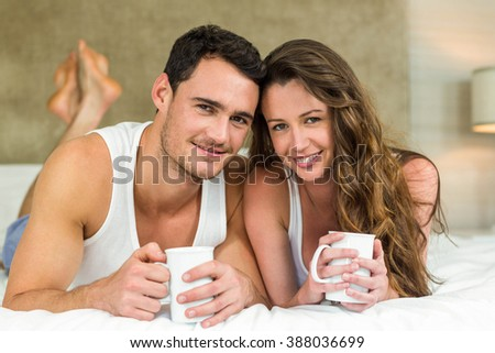 Portrait of young couple smiling and having cup of coffee on bed