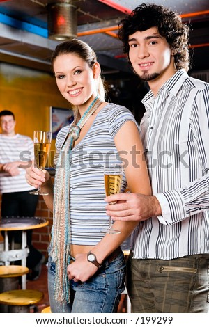 Portrait of young couple standing and holding the glasses of white wine