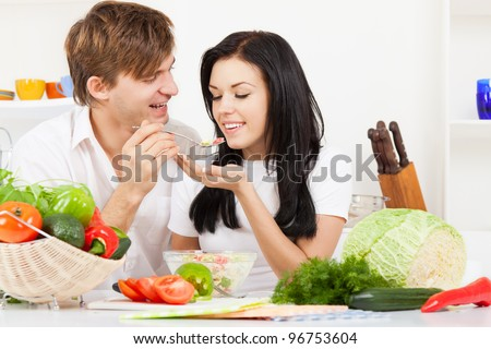 portrait of young couple tasting the meal in their kitchen happy smile, man feed woman with spoon, looking to each other - stock photo