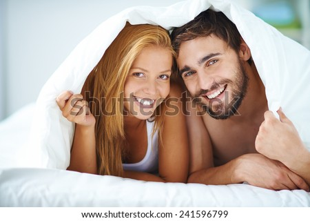 Portrait of young couple under the sheet - stock photo