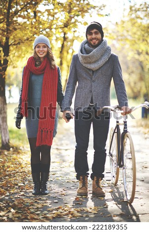 Portrait of young couple walking in autumn - stock photo