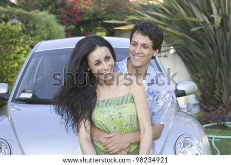 Portrait of young couple with car - stock photo
