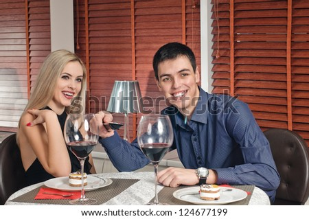 portrait of young couple with glasses of wine and remote console - stock photo